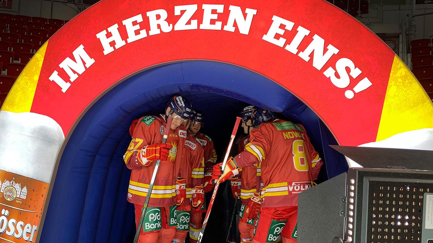 """Die Spieler der Düsseldorfer EG versammeln sich im Einlauftunnel, über dem das DEG-Motto  """"Im Herzen eins"""" ragt."""