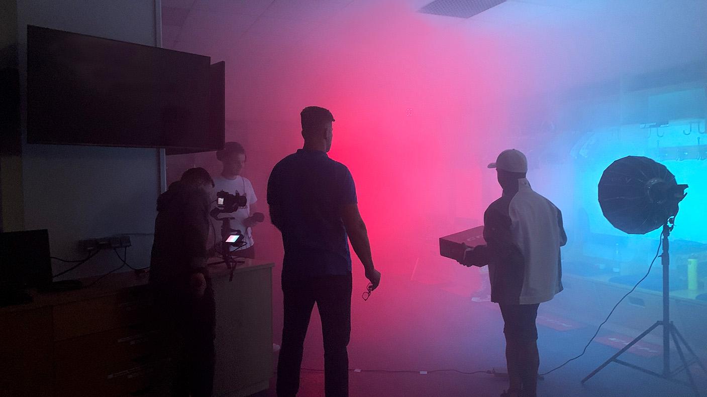 Das Filmteam der Transportbotschafter steht in der rot-blau beleuchteten Kabine der DEG und geht alle Kameraeinstellungen vorher durch.