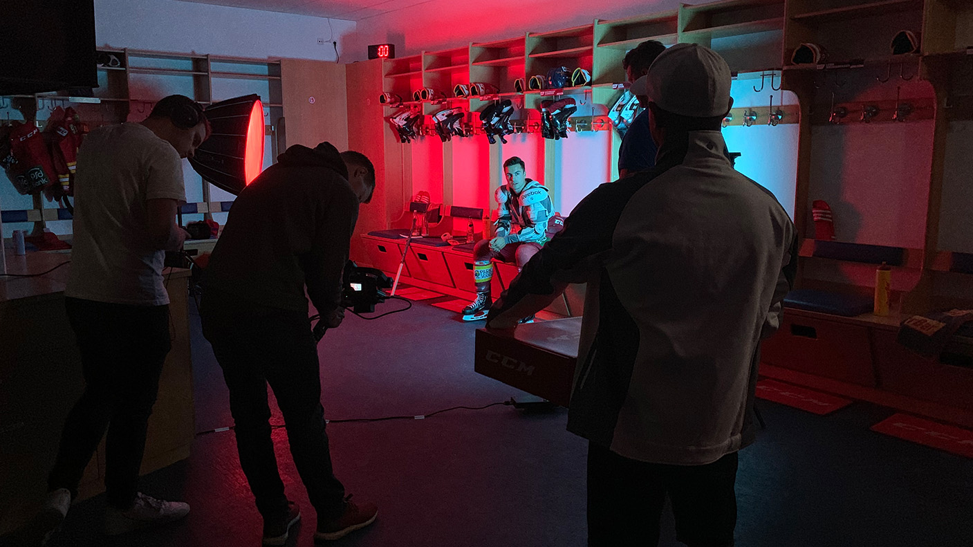 Die Kamera hat Maxi Kammerer im Fokus, der konzentriert in der rot-blau ausgeleuchteten DEG-Kabine sitzt.