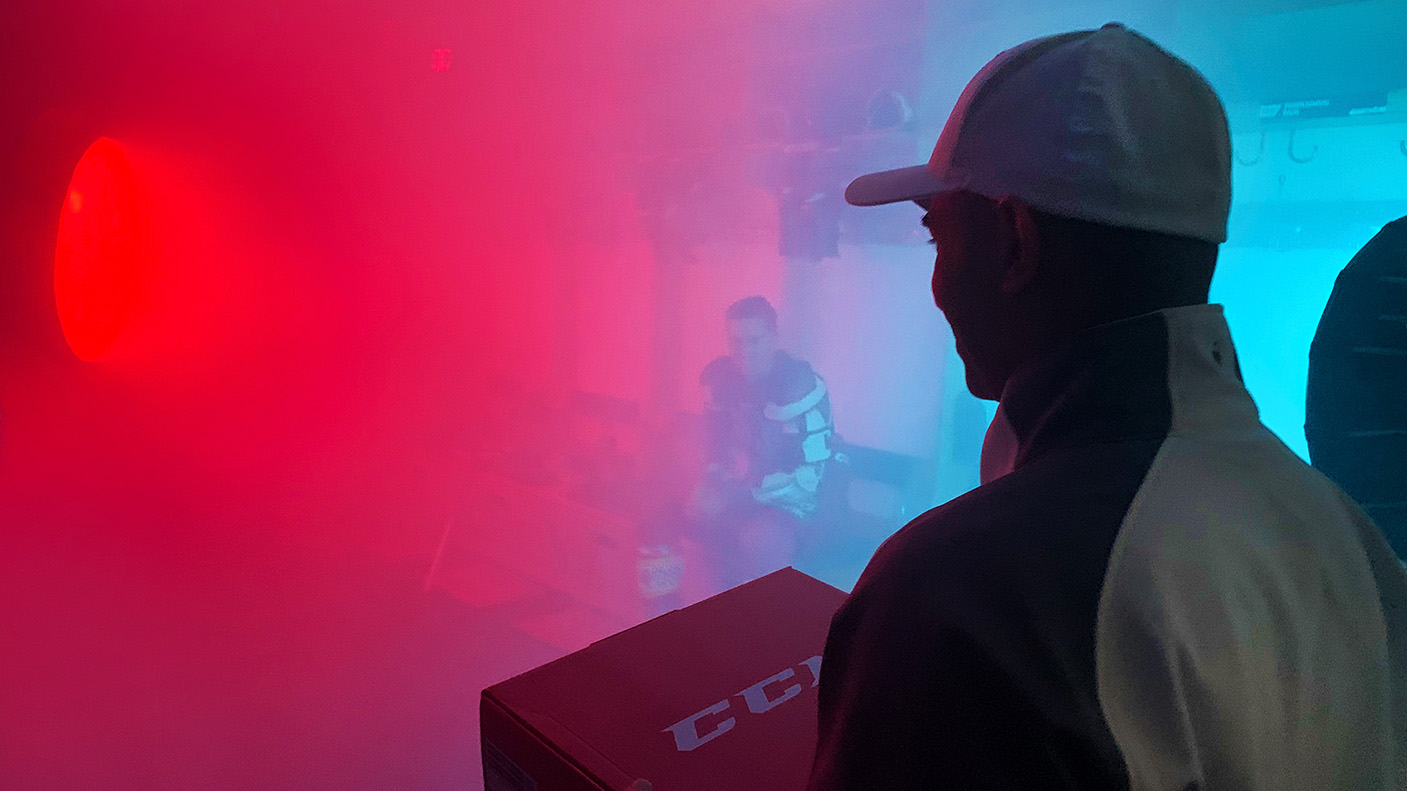 Die Nebelmaschine läuft auf Hochtouren. Der Paketbote steht bereit, um Maxi Kammerer das Paket mit dem DEG-Trikot zu übergeben.